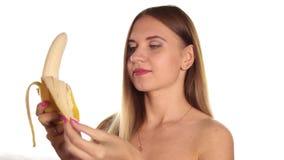 A jovem mulher despida veste o batom vermelho e tem seu cabelo para baixo, e escovado, descascando e comendo uma banana grande Al vídeos de arquivo