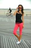 Jovem mulher desportiva que anda no passeio à beira mar Imagens de Stock