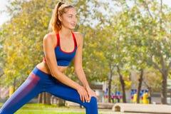 Jovem mulher desportiva que aquece-se durante o exercício fotografia de stock royalty free
