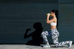 Jovem mulher desportiva que dá certo com pesos ao estar contra o fundo preto fora Imagens de Stock Royalty Free