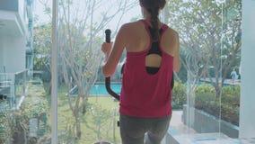 Jovem mulher desportiva que exercita na máquina da etapa no gym do condomínio vídeos de arquivo