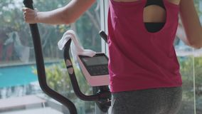 Jovem mulher desportiva que exercita na máquina da etapa no gym do condomínio video estoque