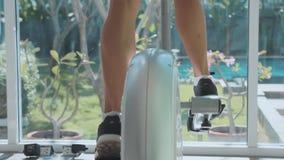 Jovem mulher desportiva que exercita na máquina da etapa no gym no movimento lento filme