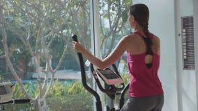 Jovem mulher desportiva que exercita na máquina da etapa no gym no movimento lento video estoque