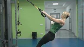 Jovem mulher desportiva que faz o exercício no gym filme