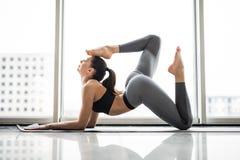 Jovem mulher desportiva que faz a prática da ioga contra janelas panorâmicos Fotografia de Stock Royalty Free