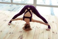 Jovem mulher desportivo que dispõe extensamente seus pés durante exercícios imagens de stock