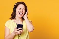 Jovem mulher despreocupada feliz que escuta a música do smartphone sobre o fundo do estúdio, música do canto gosta alto, estando  fotografia de stock royalty free