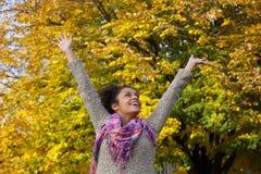 Jovem mulher despreocupada que aprecia o outono com os braços aumentados Fotografia de Stock
