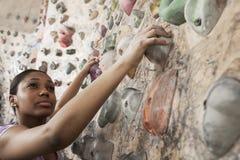 Jovem mulher determinada que escala acima uma parede de escalada em um gym de escalada interno Imagens de Stock Royalty Free