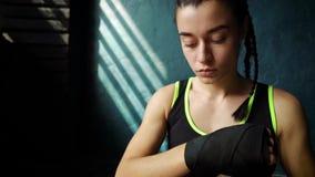 Jovem mulher do ajuste do movimento lento no assoalho, envolvendo as mãos com a fita da atadura que prepara-se para o treinamento video estoque