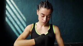 Jovem mulher do ajuste do movimento lento no assoalho, envolvendo as mãos com a fita da atadura que prepara-se para o treinamento filme