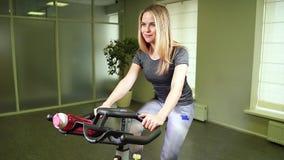 Jovem mulher do ajuste que usa a bicicleta no gym Atleta fêmea forte que faz o cardio- exercício no ciclo no health club vídeos de arquivo
