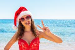 A jovem mulher do bronzeado magro no chapéu de Santa e o maiô vermelho que relaxa a areia tropical encalham conceito do feriado d fotografia de stock royalty free