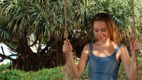 Jovem mulher do cabeleireiro do movimento lento que balança no jardim perto da praia do mar video estoque
