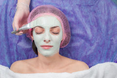 Jovem mulher do close up com máscara facial da argila no salão de beleza fotografia de stock