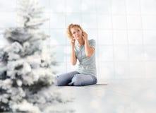 A jovem mulher do conceito do Feliz Natal escuta músicas do Natal de seu telefone celular com os telefones da orelha que sentam-s imagem de stock royalty free
