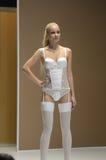 Jovem mulher do desfile de moda da expo de Lingrie nas meias e na roupa interior brancas Foto de Stock