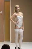 Jovem mulher do desfile de moda da expo de Moscou Lingrie nas meias brancas e no outono da roupa interior Foto de Stock Royalty Free