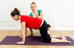 Jovem mulher do ensino do instrutor do treinador a esticar para trás na pose da vaca da ioga dos pilates no estilo de vida saudáv imagem de stock royalty free