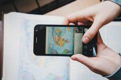 Jovem mulher do estudante que toma um livro da imagem do mapa do mundo da foto no preto da tela com Smartphone Vista superior Ter Imagens de Stock Royalty Free