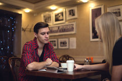 A jovem mulher do homem do moderno de dois amigos está sentando-se dentro Imagem de Stock