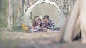 Jovem mulher do homem novo do retrato consideravelmente que encontra-se perto de se na barraca na floresta que lê o livro Partes  filme