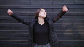 Jovem mulher do movimento lento na roupa ocasional que olha a câmera que sorri e que ri com a parede de tijolo no fundo cheerful filme