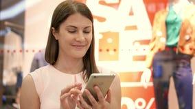 Jovem mulher do movimento lento que senta-se no sorriso do shopping Usando seu smartphone, falando com amigos vídeos de arquivo