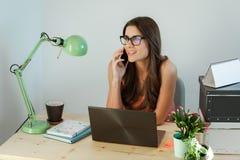 Jovem mulher do negócio que senta-se na mesa, trabalhando Imagem de Stock