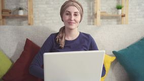 Jovem mulher do retrato com câncer em um lenço após a quimioterapia com um portátil filme