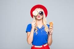 Jovem mulher do retrato da forma que faz um beijo do ar com pirulito e gelado sobre o fundo cinzento imagens de stock