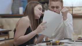 Jovem mulher do retrato e homem farpado louro que sentam-se na tabela no café que discute documentos O port?til da terra arrendad filme