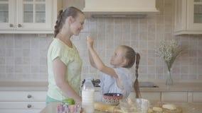 Jovem mulher do retrato e sua filha pequena que cozinham o bolo em casa na cozinha A menina que toca na cara da mãe com filme
