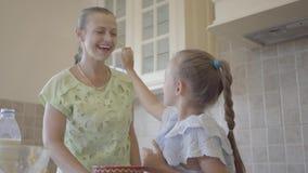 Jovem mulher do retrato e sua filha pequena que cozinham o bolo em casa na cozinha A menina que toca na cara da mãe com vídeos de arquivo