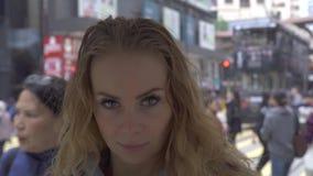 Jovem mulher do retrato no fundo da rua da cidade Mulher de cabelo vermelha bonita da cara com as sardas que olham e que levantam filme