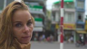 Jovem mulher do retrato no fundo da rua da cidade Feche acima da mulher bonita da cara que olha na câmera vídeos de arquivo