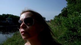 Jovem mulher do retrato nos óculos de sol na praia do verão do fundo filme