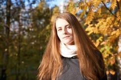 A jovem mulher do ruivo no fundo do parque para o fundo do retrato, laranja sae foto de stock royalty free