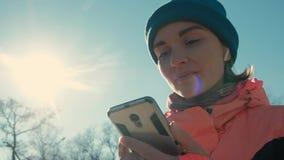 A jovem mulher do tiro da bandeja no rosa aprecia a música para o exercício exterior no inverno