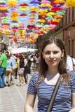 A jovem mulher do turista em uma rua decorada com colorido e abre guarda-chuvas Fotos de Stock