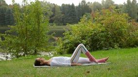 A jovem mulher dobra seu joelho ao encontrar-se em uma esteira da ioga em um banco de rio vídeos de arquivo