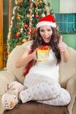 Jovem mulher doce com o presente do Natal que mostra os polegares acima Foto de Stock Royalty Free