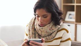 Jovem mulher doente no lenço que bebe o chá quente em casa filme