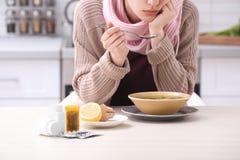Jovem mulher doente que come o caldo para curar o frio na tabela imagens de stock