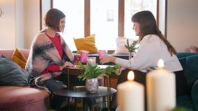 Jovem mulher dois que senta-se no café, falando e rindo ao beber o café Interior moderno bonito filme