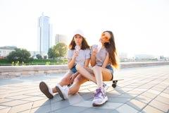 Jovem mulher dois que senta-se no sorriso feliz do skate Os amigos brincalhão apreciam o dia ensolarado Urbano exterior Modelo bo imagens de stock royalty free