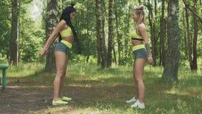 Jovem mulher dois que squatting no parque Modelos da aptidão com o exercício da tatuagem exterior vídeos de arquivo