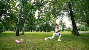 A jovem mulher dos esportes é treinar, fazendo ostenta no parque Fazer da menina da aptidão investe contra no parque no verão filme