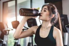 A jovem mulher dos esportes com o cocktail da proteína no abanador senta-se no gym Fotos de Stock